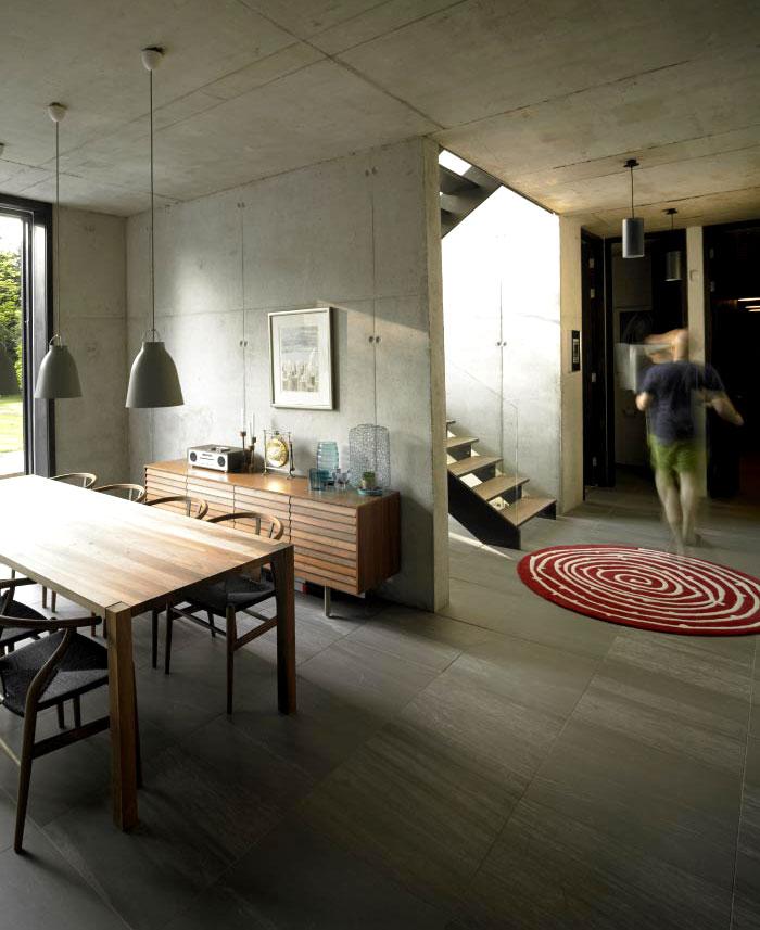 concrete-walls-wooden-furniture-stone-floor-tiles-patterned-rug
